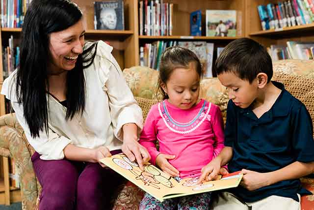 A teacher points to pictures in a children's book as she smiles at two young children sitting on a couch in a library at a public school.