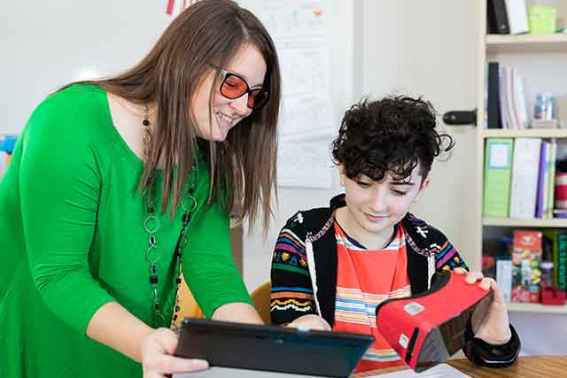 Dr. Lauren Eutsler demonstrates the use of virtual reality goggles to a 6th grade student.