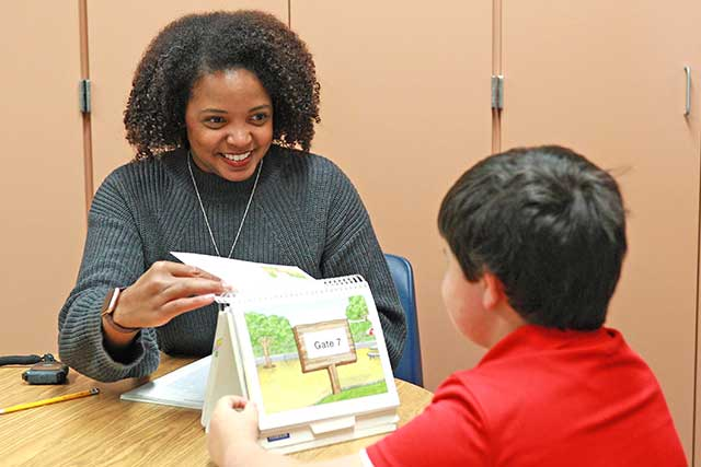 UNT graduate Elizabeth Atkins, and Educational Diagnostician with the Carrollton-Farmers Branch ISD, works with a students.