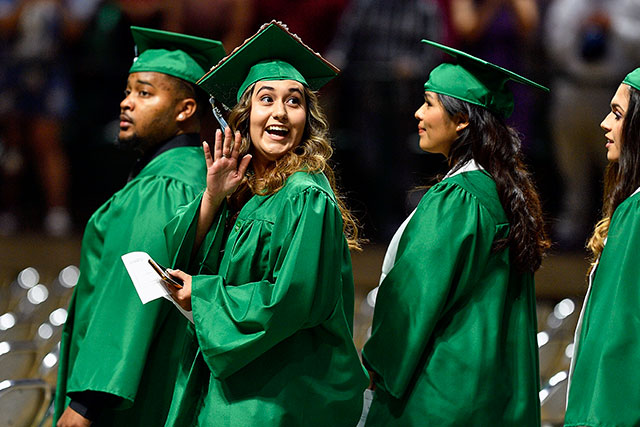 A graduate waves at family and friends during the College of Education commencement ceremony