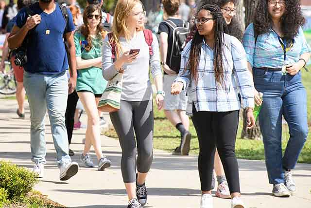 Students talk while walking across the University of North Texas campus on a sunny day.