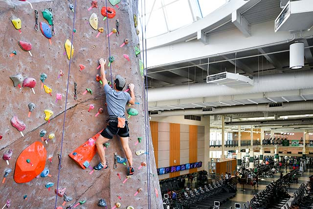 A man climbs the rock wall inside the Pohl Recreation Center on the UNT campus