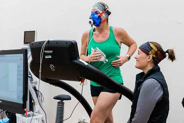 A student runs on a treadmill while wearing a monitoring device over her mouth a nose as a graduate assistant observes.