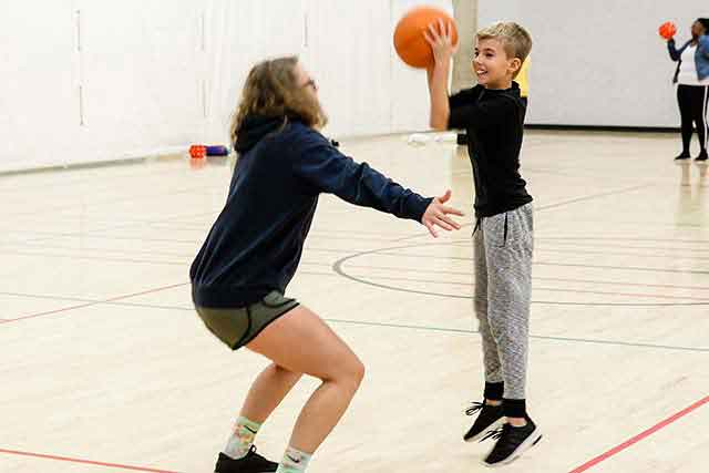 A young boy attempts to shoot a basketball over the head of a UNT student during a class on campus.