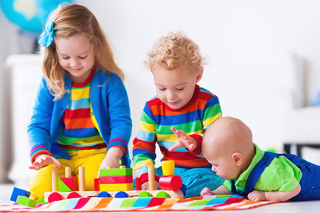 Children playing with colorful toys on a blanket