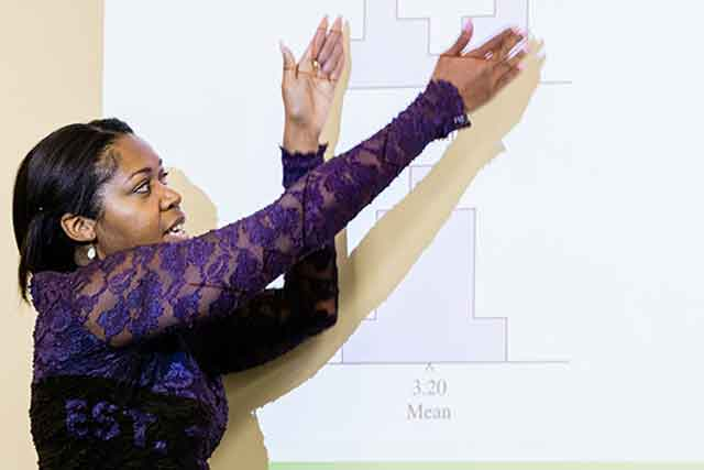 A UNT graduate student points to graphs displayed by a project as she explains their meanings.