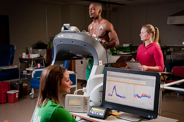 A man runs on a treadmill while being monitored by two students using state-of-the-art equipment