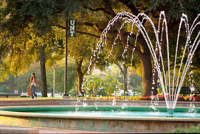 UNT students walk past a fountain