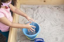 A child plays in a sandbox at the Center for Play Therapy's outdoor playroom