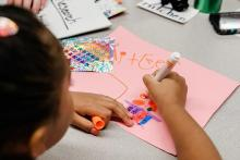 A child uses markers to draw on construction paper.