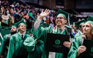 UNT student waves during graduation ceremony