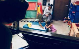 A participant in Play Therapy training peers through a two-way mirror as a counselor observes a child playing as part of therapy.