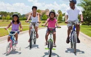 A family rides bicycles through a neighborhood.