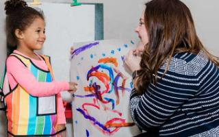 A child paints on paper while a therapist looks on